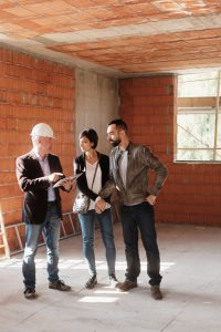 Sales agent talking with clients in new building. Man working as realtor in construction site with customers. Real estate broker showing home to husband and wife.